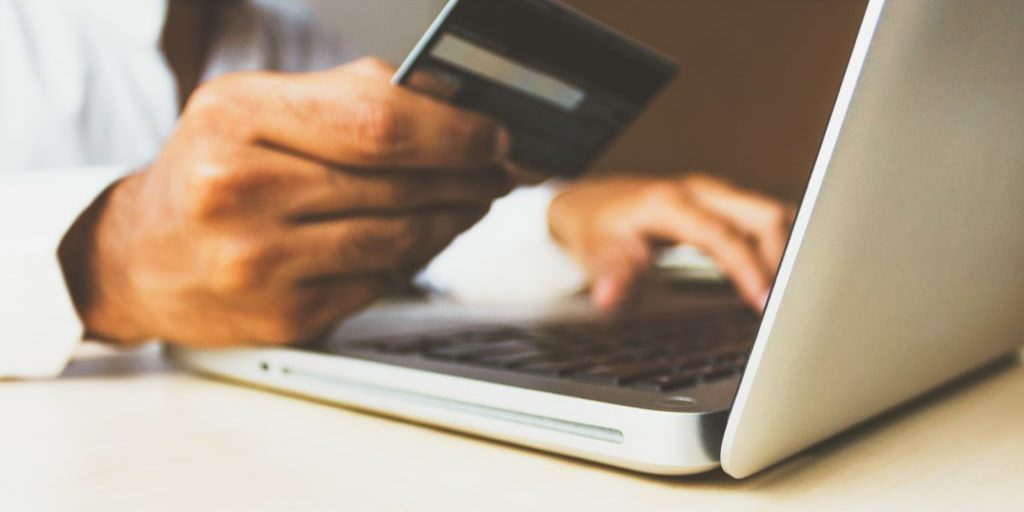Man looking at his credit card to make an online purchase because of an effective digital content marketing plan.
