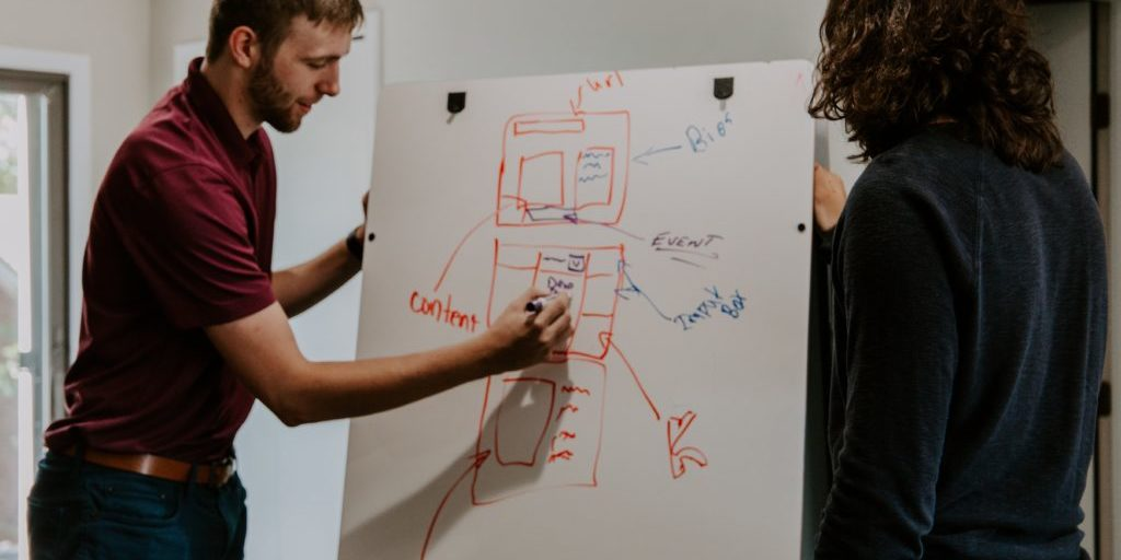 Colleagues standing at a white board talking about their content integration in digital marketing.